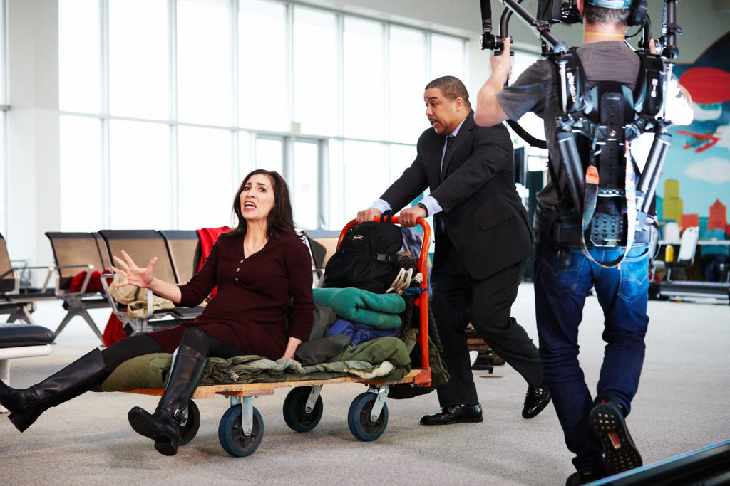 Crew filing a woman being pushed by a man while sitting on a baggage cart