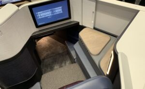 Elements' Business Class suite with IFE screen, suite door and footwell in view