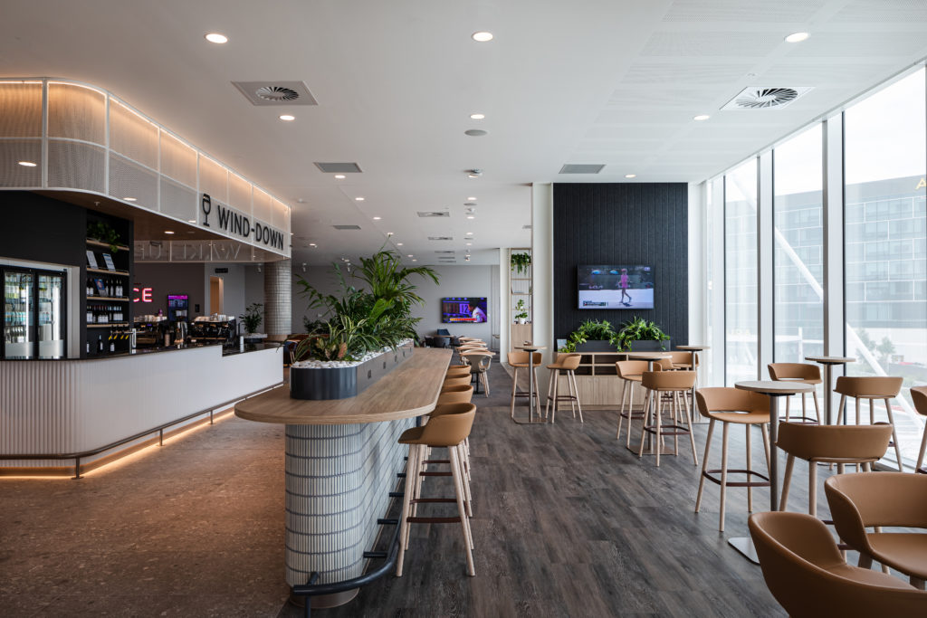 Coffee bar in the Virgin Australia lounge with high stools and large windows behind it.