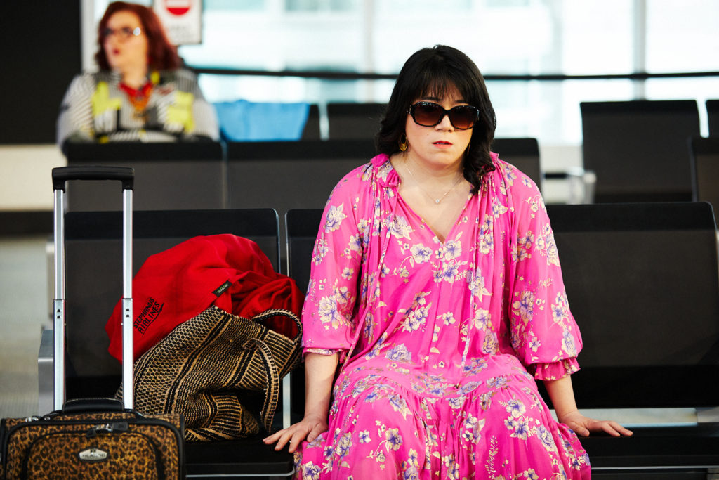 Woman dressed in a pink flower dress on set, sitting on a seat that is made to look like an airport terminal.