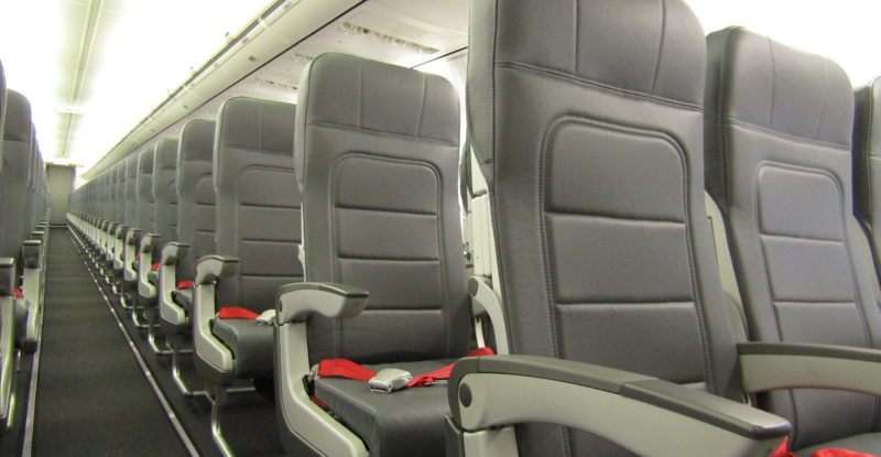 Rows of TSI seats aboard a 737-800 operated by AnadoluJet. The seats are dark grey and feature red seat belts.