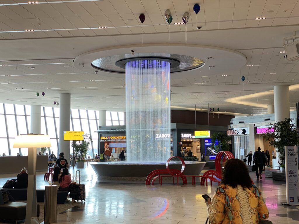 Circular water fall cascading from the ceiling in front of LaGuardia food court.