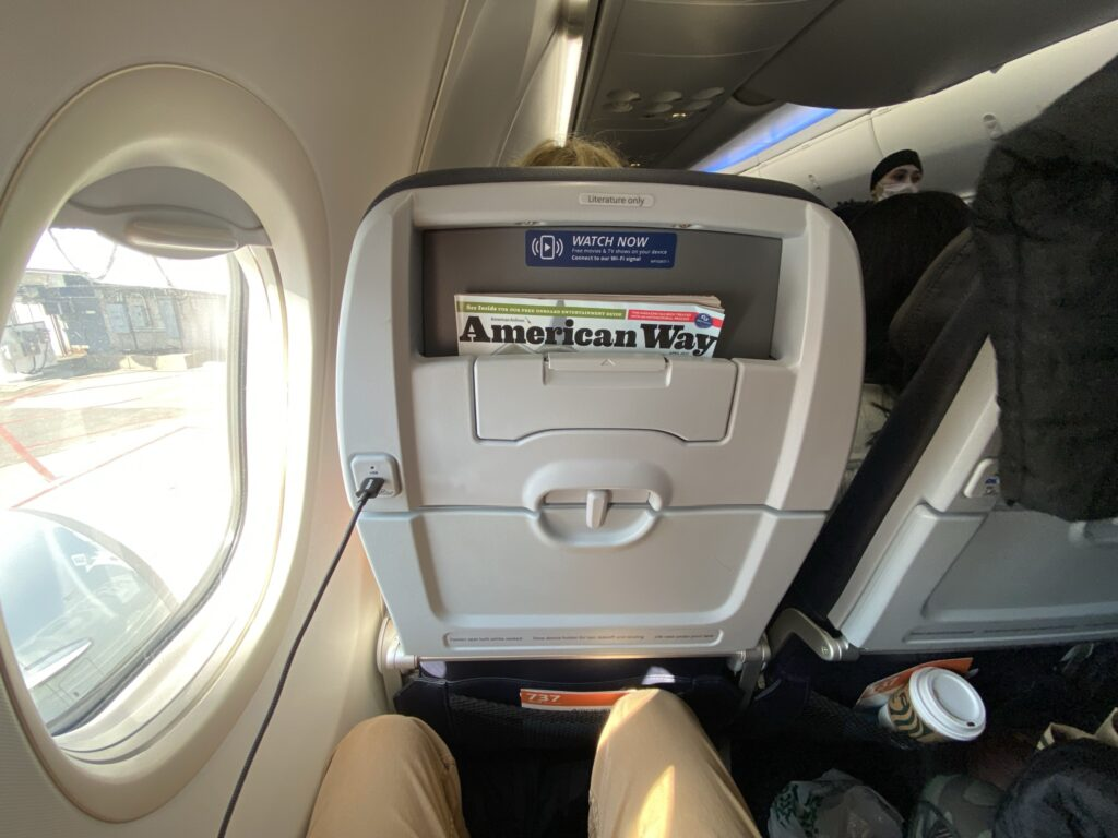 Seatback on the American Airlines Boeing 737-800 in economy class with a ped holder and power port. Man's knees show that there is little space to move.