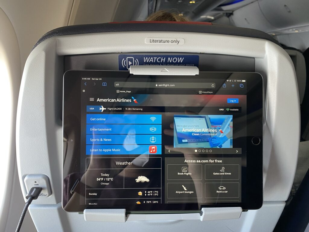 PED holder on the back of an economy class seat being used. Device is showing the IFE selection on board American Airlines.