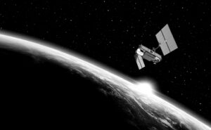 Black and white image of a satellite in orbit over a glowing earth.