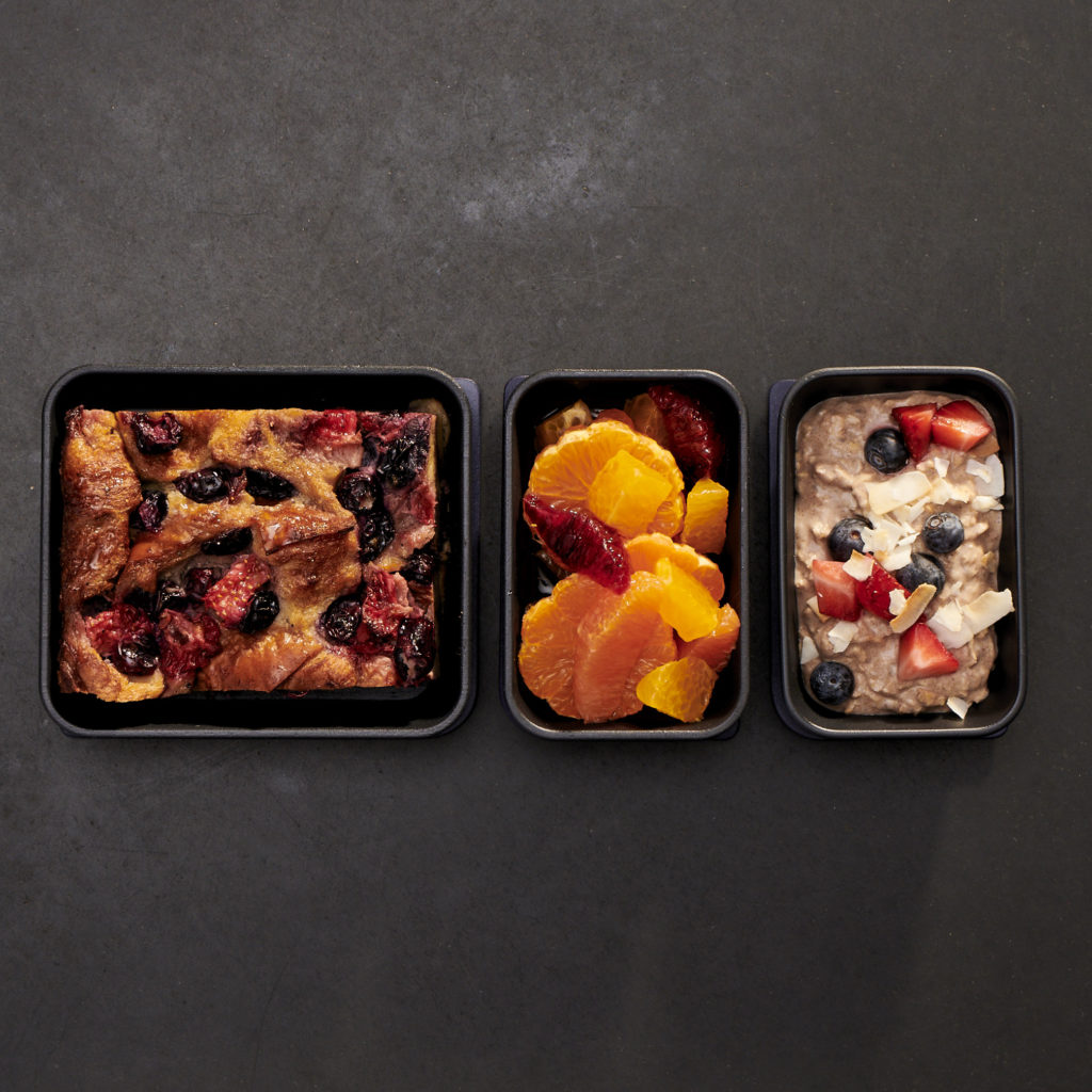 A display of 3 breakfasts in reusable dishes on a charcoal backdrop