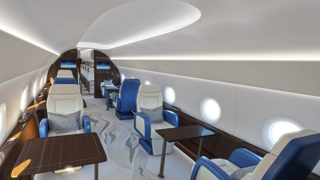 The interior of the passenger cabin with white seats, blue backing and armrests, and wood tables.