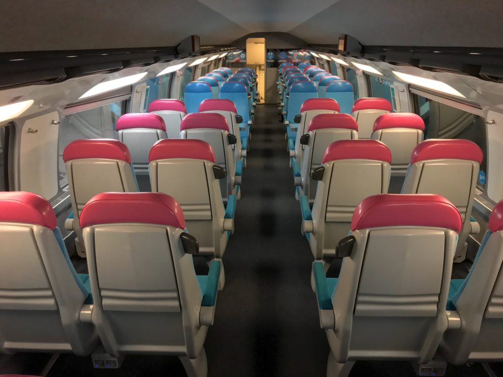 Interior of Ouigo with 2-2 configuration seats that are white with red headrests.