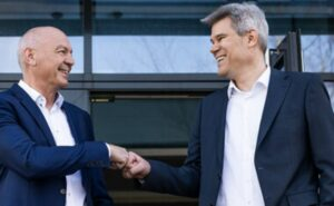 Two men in suits fist bumping in front of a building. Josef Köcher new CEO. image: Diehl Aviation