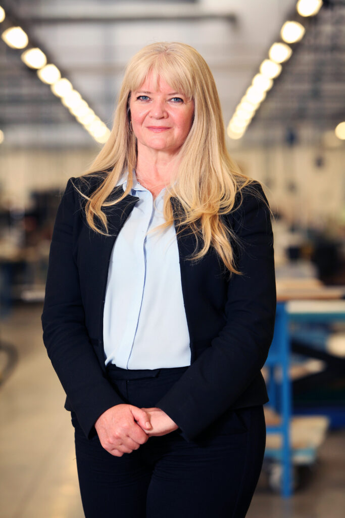 Elizabeth Payne full body photo in a suit on the factory floor.
