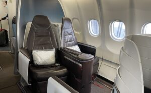 Hawaiian Airlines' first class seat, deep brown leather and the white curved seat shell.