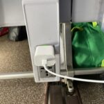 AC charger plugged into the power port offered at the base of the aircraft seat.