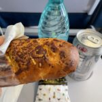 BBQ chicken and cheese sandwich with a bottle of water and a can of diet coke all displayed on an aircraft tray table.