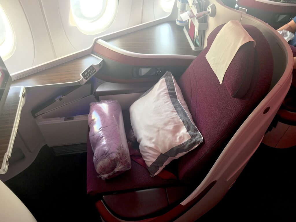 Qatar's Super Diamond seat, red with light cascading onto it through an aircraft window.