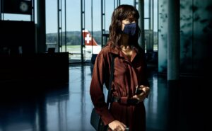 A women in an airport terminal with a mask on and a swiss aircraft in the background, IATA