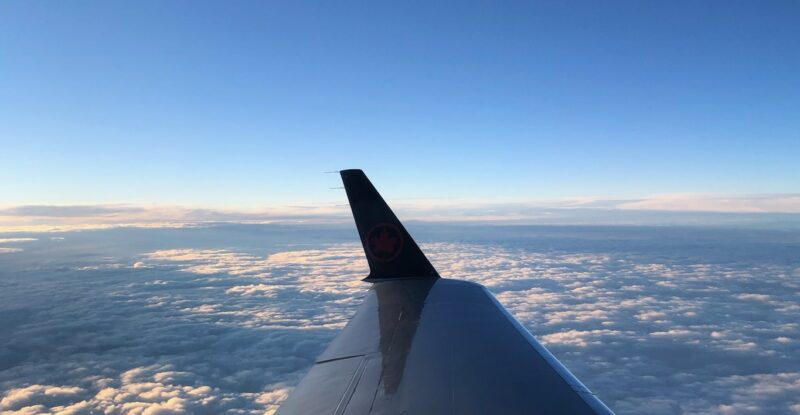 Aircraft flying over Canada, photo shows wing of aircraft through the cabin window