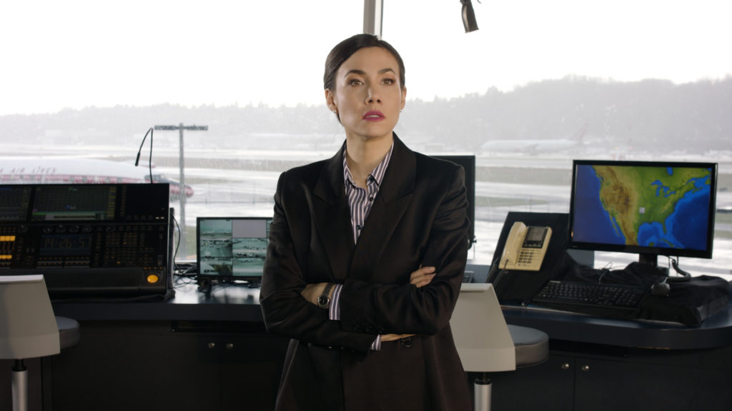 Sharleen Joynt (Controller), with her arms crossed in front of ATC screens. Video still by Kyle Seago