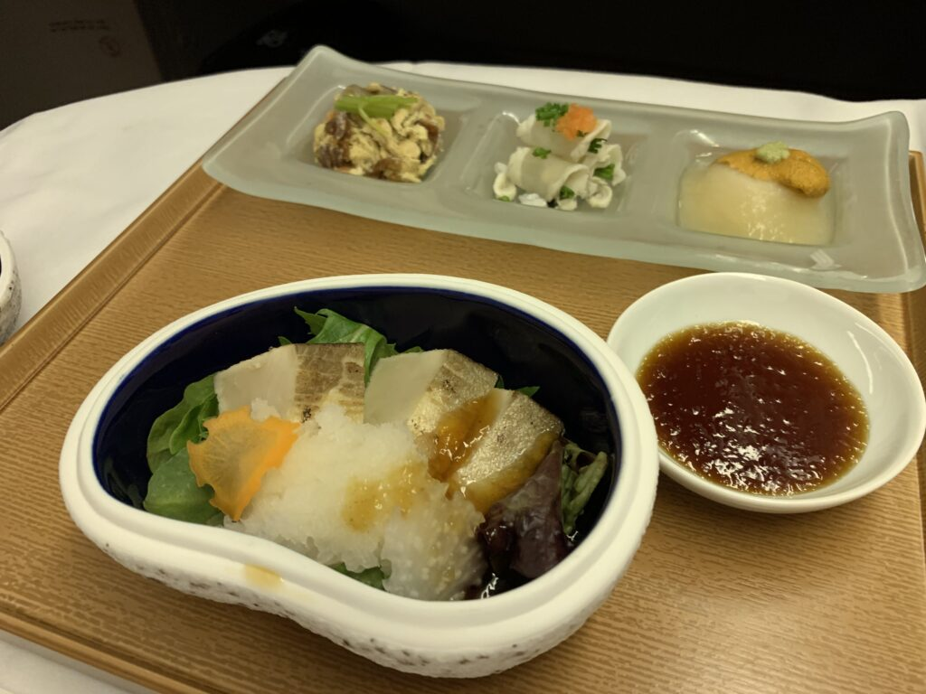 First Class Japanese meal being served on a aircraft tray table in a larger bowl with a smaller bowl of sauce on the side. Also a long dish with 3 seperate items on it.