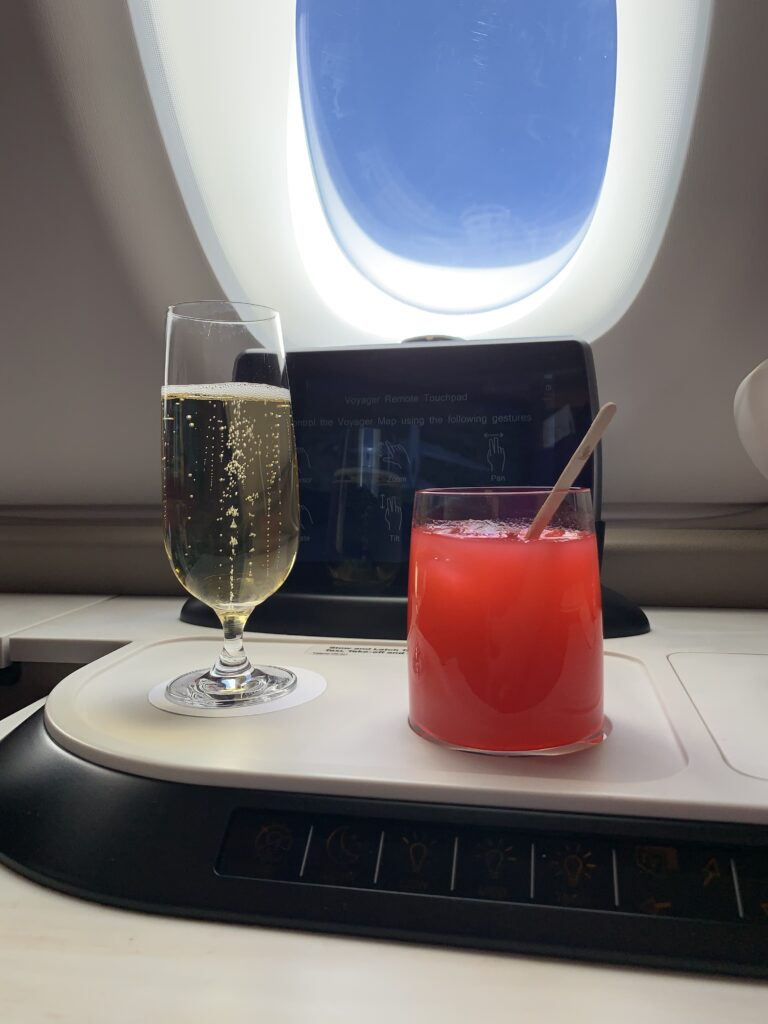 Two drinks on a first class tray table in front of an aircraft window. One glass is full of a sparking wine and another glass is full of a cocktail or pink juice. Singapore Airlines Serviceware