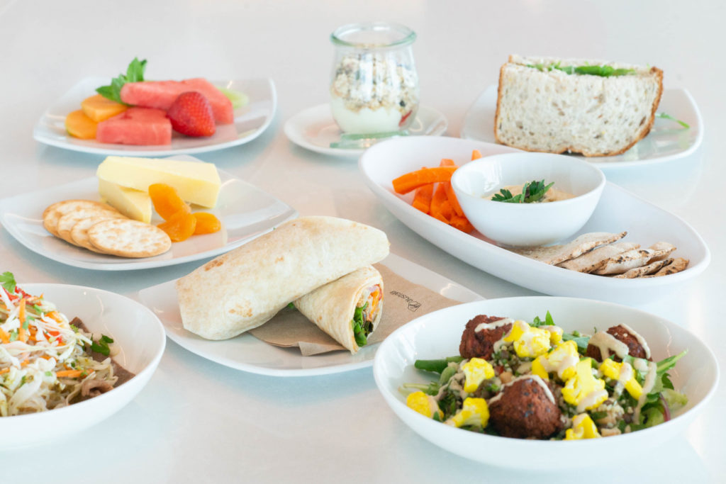 A display of food on white dishes: wraps, salads, sandwiches, and cheese.
