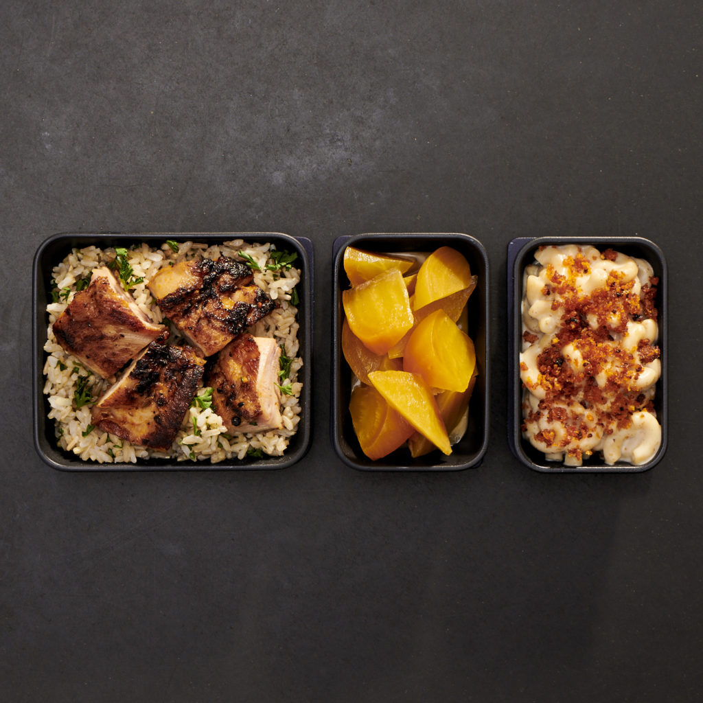 A display of 3 meals in reusable dishes on a charcoal backdrop.