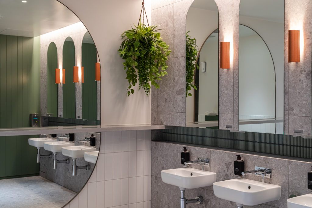 A line of bathroom sinks on a grey marble wall and arch shaped mirrors atop.