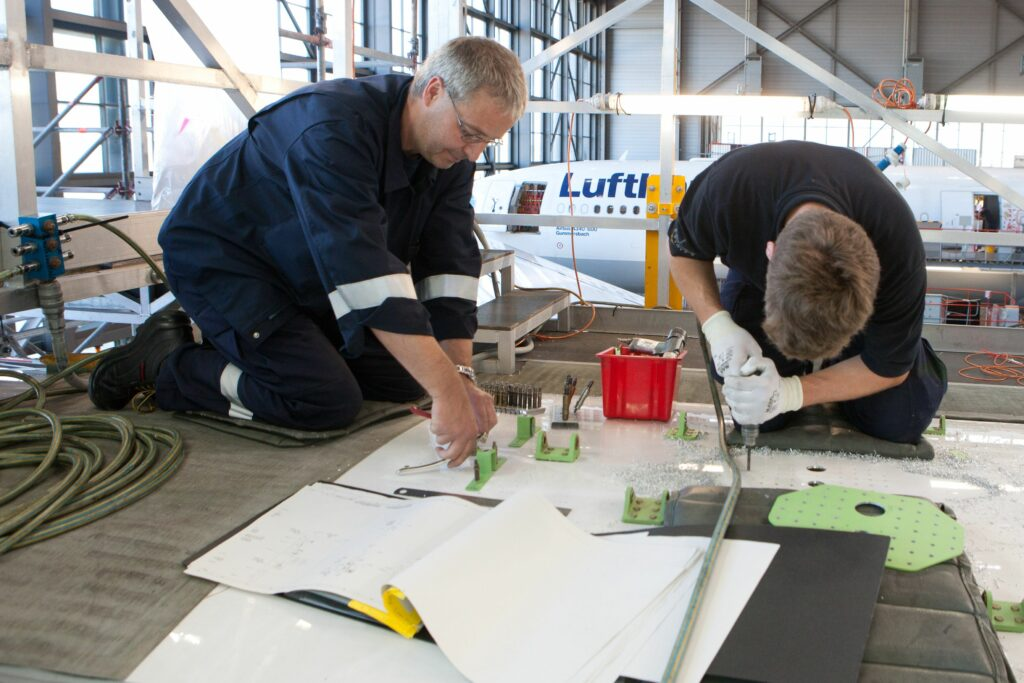 Two men on the ground in an aircraft hanger working on a part.