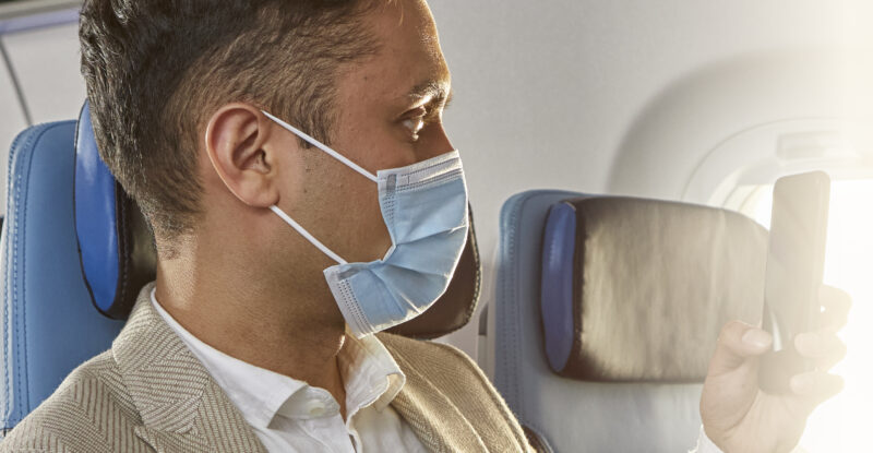 KLM customer inflight, masked, and looking at a mobile device.