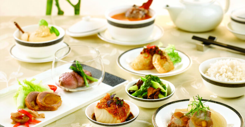 Singapore Airlines serviceware being displayed on a cream table cloth. Multiple different dishes are pictured.