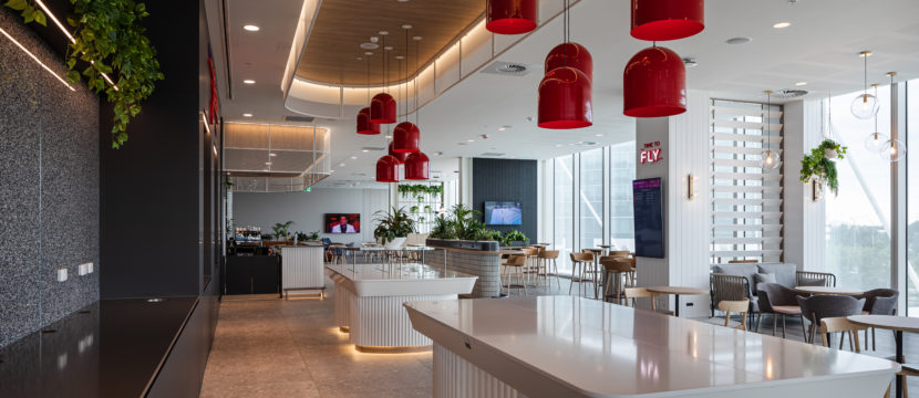 Virgin Australia lounge with light wood flooring, red lanterns hanging from a high ceiling, buffet style tables and lots of various seating to a backdrop of large bright windows.