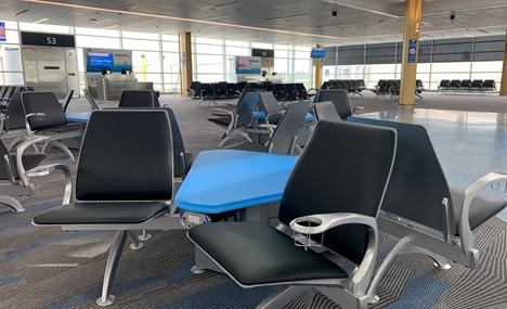 Interior view of the new 14-gate concourse seating area. Grey Seats with blue middle tables.