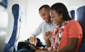 Man and Woman in flight looking at a mobile device.