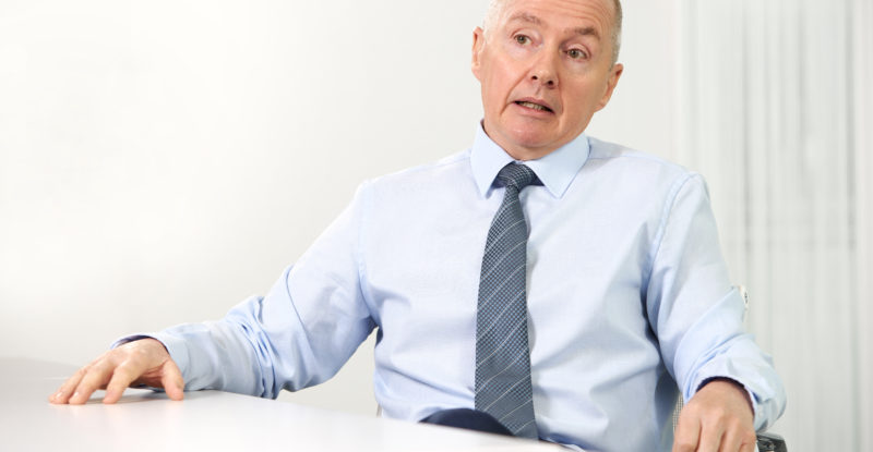 Photo of Willie Walsh sitting at a table in a suit.