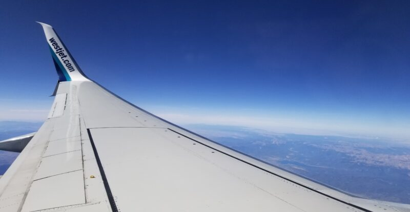 WestJet Wing tip view from the aircraft window of the 737-800. The view is at daytime with clear blue skies.