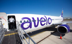 Avelo aircraft at the gate with an entry ramp extended for passenger to walk on.