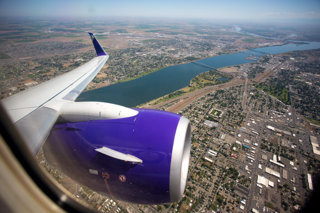 View out the window for an aircraft inflight. You can see the purple livery on the engine.