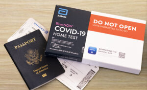 US Passport, boarding pass and a at home COVID testing kit set out on a table.