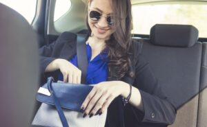 Businesswoman in a taxi sitting on back seat.