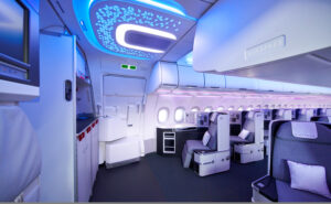 Airbus Airspace cabin showing the entryway, geometric design on the ceiling, blue and purple shades cast by LED lights and business class seats in greys and purple. Seats are in a 1-1 configuration.
