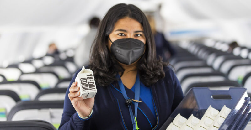 Female Alaska Airlines flight attendant wearing a mask and holding up a boxed water product onboard an aircraft.