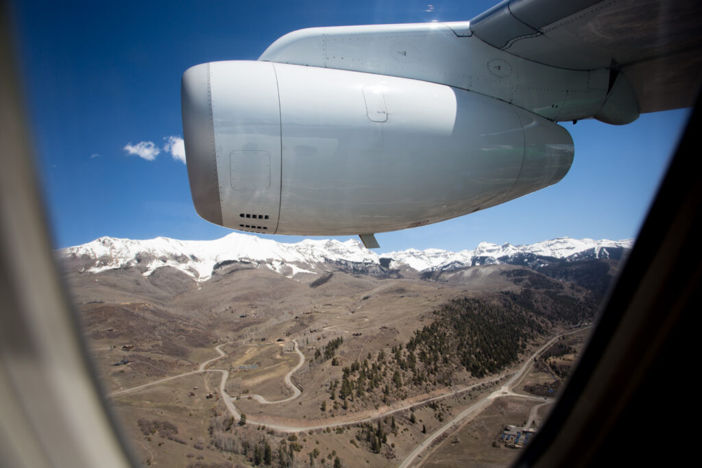 View from the window of Denver Air Connection's Dornier 328JET showing the engine and a mountian view.
