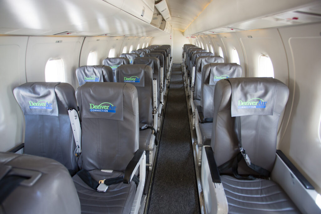 Denver Air Connection Dornier 328JET interior in a 1-2 configuration. Seats are grey and walls are white.
