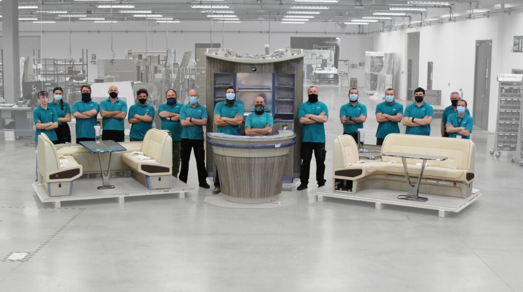 The AIM team stands beside the 123rd shipset in the AIM factory