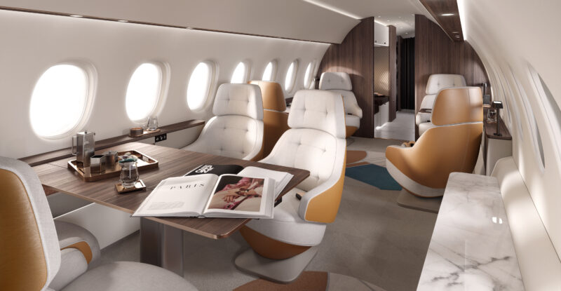 Falcon 10X interior showing 8 seats in cream with light brown details. A carpet with geometric shapes on it.