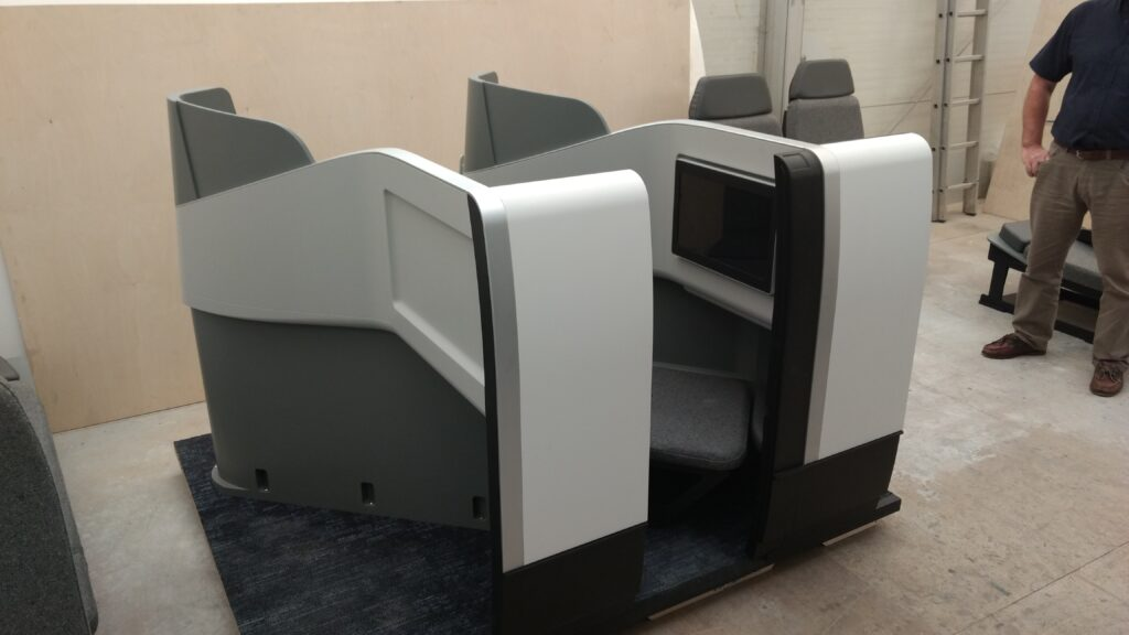 Herringbone business class seat in grey and white displayed on a show floor.