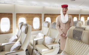 An Emirates flight attendant stands alongside the carrier's new premium economy seats, which are covered in cream anti-stain leather.