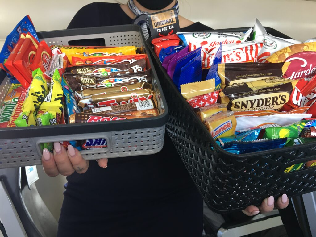 Aircraft crew holding a variety of snacks in two baskets.
