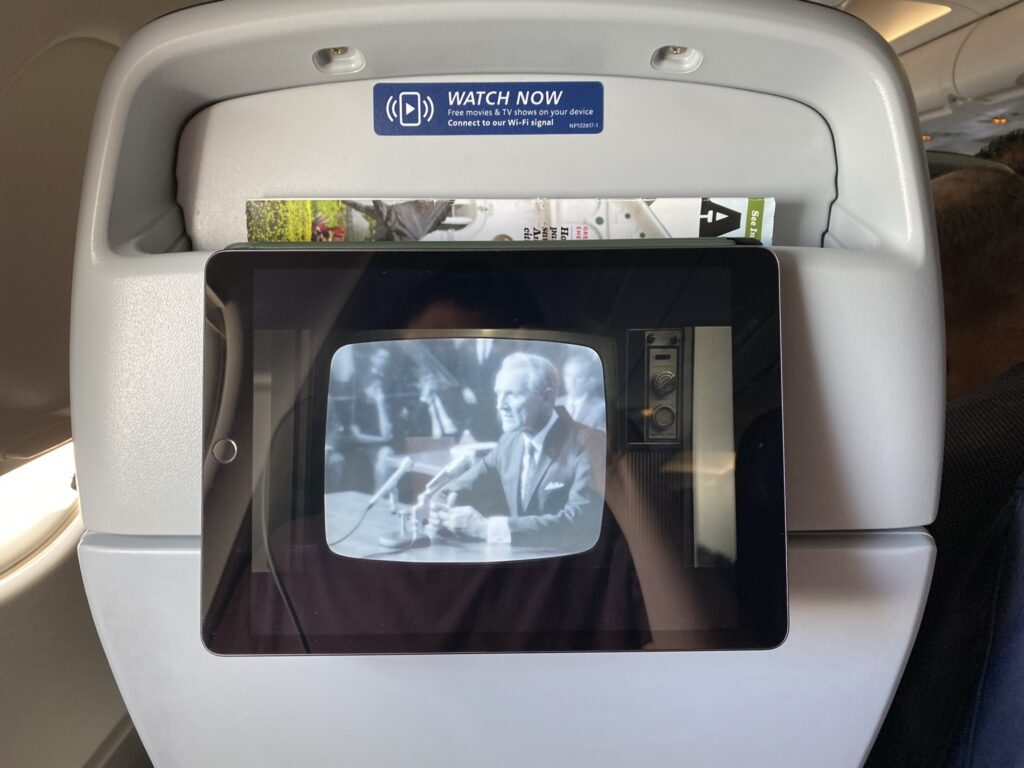 Ipad being held up on an aircraft seatback in the literature pocket.