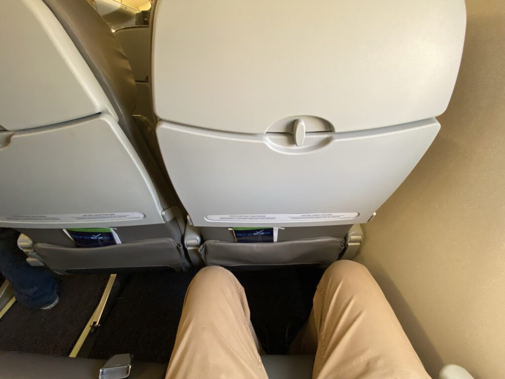 The author shows how much legroom he has in the Breeze economy seat; he has a few inches of knee clearance