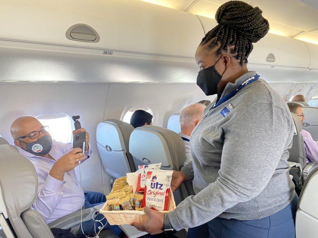 A female flight crew hands UTZ snacks to an aviation enthusiast aboard the flight